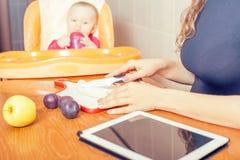 Mère recherchant la recette de la préparation de l'aliment pour bébé Images stock
