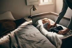 Mère regardant son bébé dormant dans une huche photo libre de droits