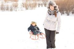 Mère remorquant son fils dans la neige Images libres de droits