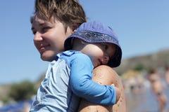 Mère retenant son enfant en bas âge sur une plage Photo stock