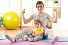 Mère riante folâtre avec le bébé et haltères dans des mains La maternité n'est pas une cause pour se laisser disparaître Image stock