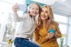 Mère satisfaite et fille prenant des selfies Photos stock