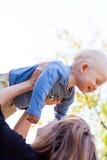 Mère se soulevant vers le haut de son fils mignon Image stock