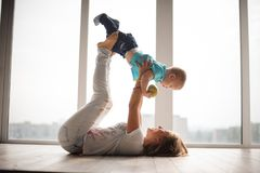 Mère, se trouvant sur le plancher, tenant son petit fils dans le ciel Photographie stock libre de droits