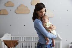 Mère soulageant le fils nouveau-né de bébé dans la crèche Photos libres de droits