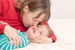 Mère soulageant son petit fils pleurant Image libre de droits