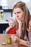 Mère soumise à une contrainte essayant d'alimenter le bébé tatillon image stock