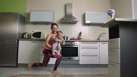 Mère sportive faisant des mouvements brusques avec le fils riant de bébé banque de vidéos
