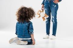 mère stricte d'afro-américain avec le jouet se tenant devant sa fille qui s'asseyant photographie stock
