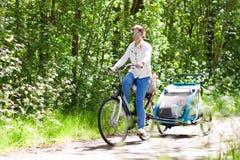 Mère sur la bicyclette avec la remorque de vélo de bébé en parc photographie stock libre de droits