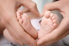 Mère tenant des pieds de bébé, photographie stock