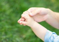 Mère tenant la main d'un petit enfant photo stock