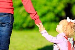 Mère tenant la main de la petite fille dehors photographie stock