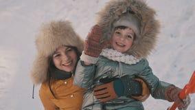 Mère tenant la petite fille mignonne appréciant Sunny Weather froid en parc d'hiver banque de vidéos