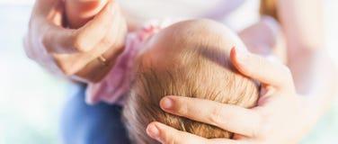 Mère tenant la tête de bébé aux mains Photos stock