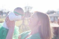 Mère tenant le bébé à la lumière du soleil lumineuse images libres de droits