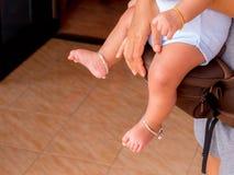 Mère tenant le bébé dans des transporteurs Image stock