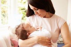 Mère tenant le bébé garçon de sommeil à la maison Image libre de droits