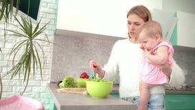 Mère tenant le bébé sur des mains dans la cuisine La maman avec l'enfant préparent le dîner banque de vidéos
