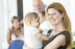 Mère tenant le bébé sur le porche avec la famille derrière Photographie stock