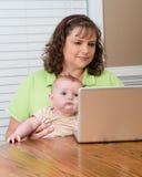 Mère tenant le bébé tout en travaillant sur l'ordinateur Image libre de droits