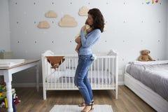 Mère tenant le fils nouveau-né de bébé dans la crèche Photo stock