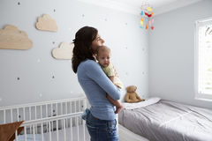 Mère tenant le fils nouveau-né de bébé dans la crèche Image stock