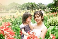 Mère tenant sa fille dans le jardin photo libre de droits