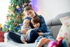 Mère, tenant ses deux enfants, s'asseyant sur le divan Images libres de droits