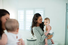 Mère tenant son bébé dans la salle de bains Image stock