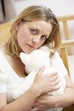 Mère triste s'asseyant dans la pépinière vide image stock