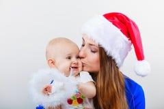 Mère utilisant le chapeau de Santa tenant le bébé Photo libre de droits