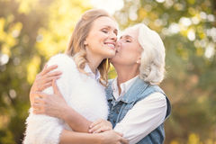 Mère vieillissante embrassant la fille affectueuse en parc Photographie stock