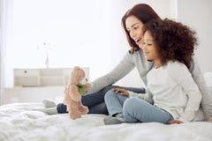 Mère vigilante et fille regardant le jouet Image stock