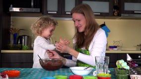 Mère vilaine et fille mignonne avec les visages sales de chocolat dans la cuisine clips vidéos