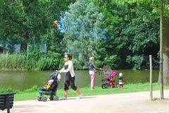 Mères avec des enfants en stationnement de ville Image stock