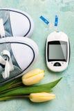 Mètre, chaussures en caoutchouc et tulipes de glucose Photos stock