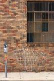 Mètre de fenêtre barré par façade de brique rouge Photos libres de droits