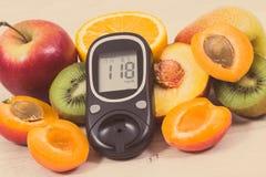 Mètre de glucose avec le niveau de sucre de résultat et fruits nutritifs en tant que dessert sain pour des diabétiques images stock