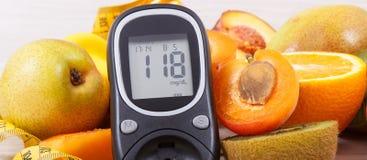 Mètre de glucose avec le niveau de sucre de résultat et fruits nutritifs en tant que dessert sain pour des diabétiques images libres de droits
