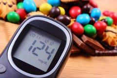 Mètre de glucose avec le tas des bonbons sur la surface en bois, le diabète et la nourriture malsaine Images libres de droits