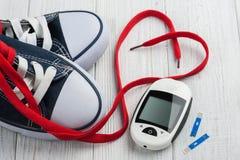 Mètre de glucose, chaussures en caoutchouc, coeur rouge Images stock
