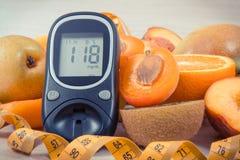 Mètre de glucose pour examiner le niveau de sucre, le centimètre et les fruits nutritifs en tant que dessert sain pour assurer le photo libre de droits
