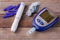 Mètre de glucose sanguin sur un vieux fond en bois Photographie stock libre de droits