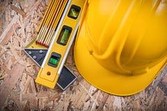 Mètre en bois carré de casque antichoc de niveau de construction de règle sur OSB Photographie stock libre de droits