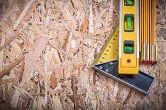 Mètre en bois de règle de niveau carré de construction sur OSB Photographie stock libre de droits