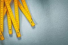 Mètre en bois jaune sur le concept concret de construction de fond Image libre de droits