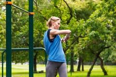 Mètre intelligent d'impulsion de montre de jeune fille sportive attirante en parc Étirage des mains Photo stock