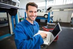 Mécanicien à l'aide d'un ordinateur portable pour travailler Photo stock