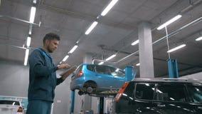 mécanicien à l'aide d'un PC de comprimé au service de garage de réparation Photographie stock